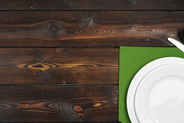 Сервировка стола с тарелками на темном деревянном фоне