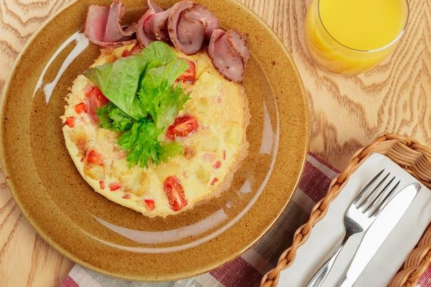 おいしい朝食。スライスしたハムと揚げたオムレツをクローズアップ