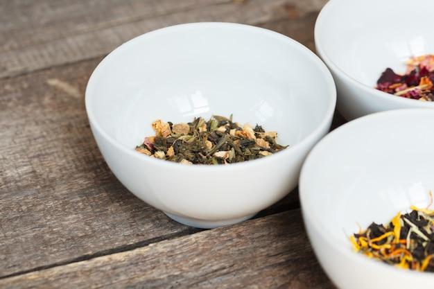 木製の背景にボウルで芳香族乾燥茶