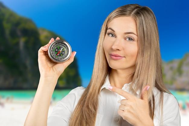 美しい若い女性は彼女の顔の近くにコンパスを保持しています。概念