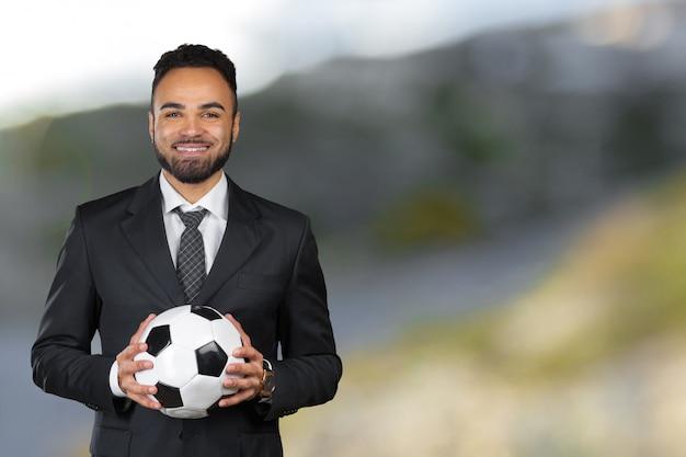Африканский бизнесмен держит футбольный мяч. футбольный тренер