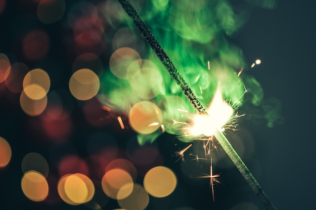 Крупный план зеленого праздника спарклер в темноте