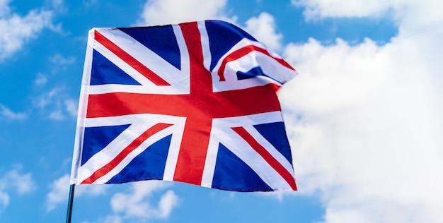 Великобритания флаг развевается на ветру в голубом небе