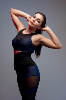 Портрет молодой женщины фитнеса в спортивной одежде позирует в студии