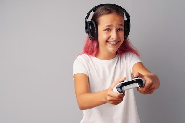 Молодая красивая девушка играет с консолью джойстик над серым