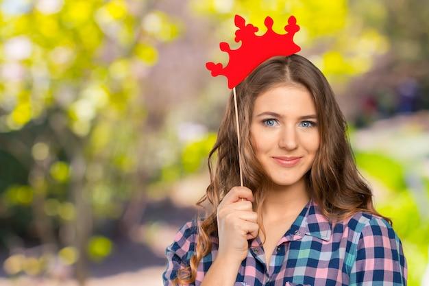 彼女の頭の上のお祝い紙の冠と美しい若い女の子のポートレート、クローズアップ
