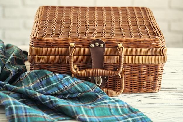 Закройте вверх деревянной корзины с посудой на белой таблице