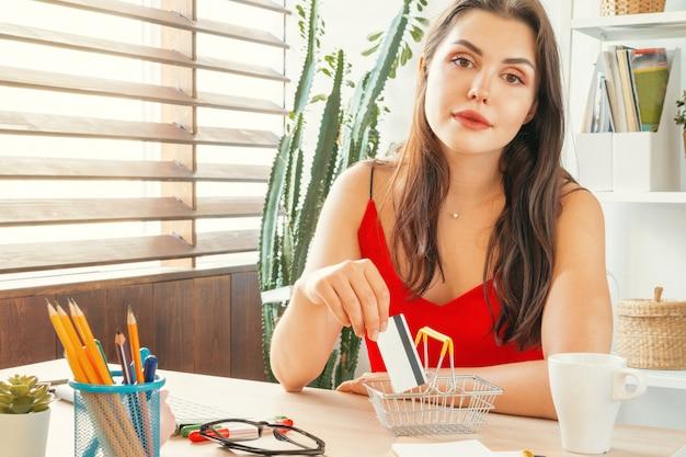 コンピューターのモニターで家のテーブルに座っている女性とのオンラインショッピング