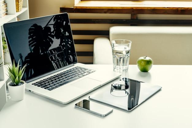 Раскройте компьтер-книжку на таблице около софы, домашнего интерьера. фрилансер на рабочем месте