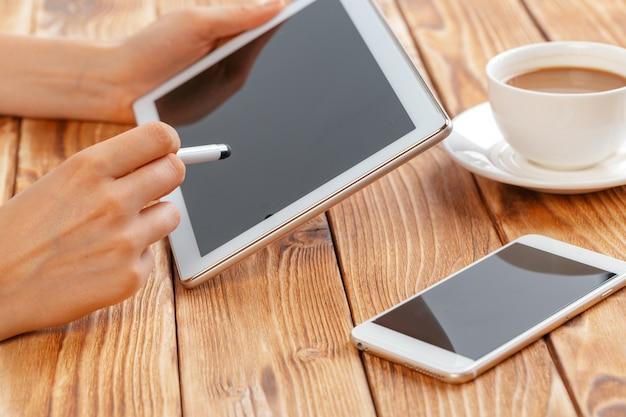 デジタルタブレットを押しながら朝のマキアートを飲む若い女性の手のクローズアップ。