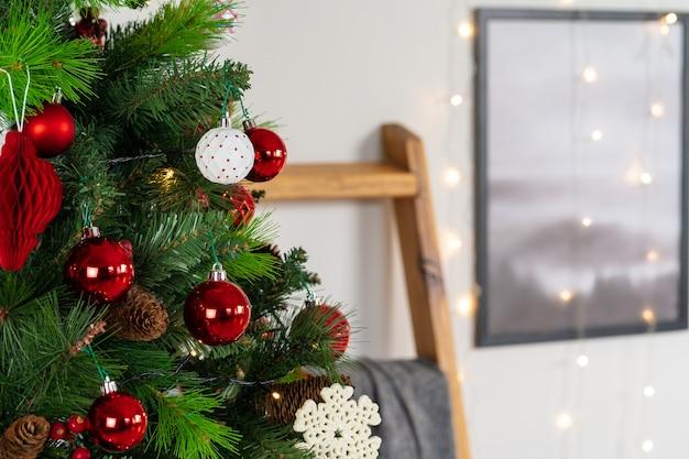 クリスマスツリーからぶら下がっている赤と白のつまらないものをクローズアップ