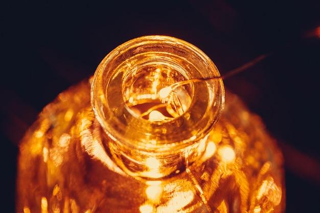 Рождественские огни гирлянды положить в бутылку в темноте крупным планом