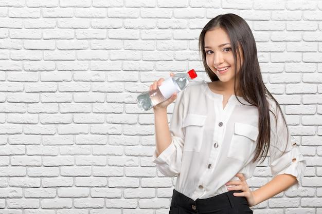 水のボトルを示す若い女性