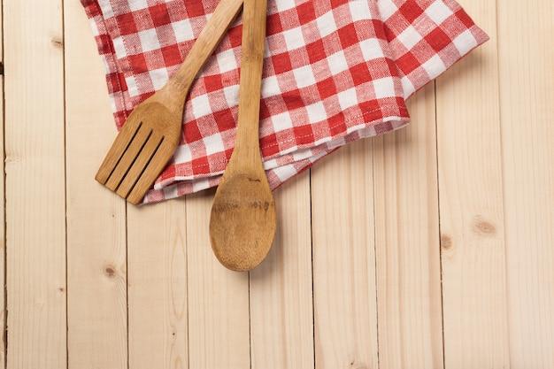木製のスプーンや台所のテーブルに赤いナプキンを使った他の調理器具、