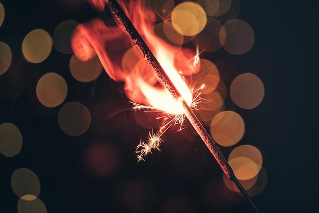 Красные бенгальские огни сверкают крупным планом на темноте