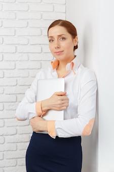 Портрет молодой женщины, используя ноутбук в офисе