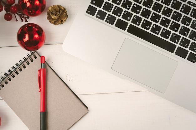 クリスマスの装飾が施されたテーブルの上のメモ帳とコンピューターを開く