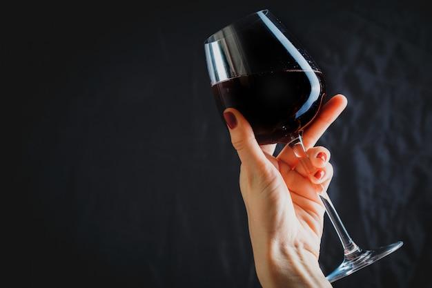 Рука бокал красного вина на темно-серой поверхности
