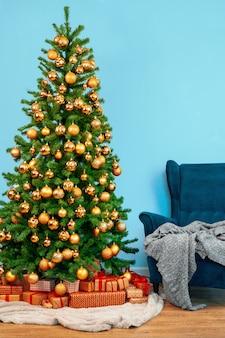 Интерьер праздника, красивая украшенная елка с синим креслом