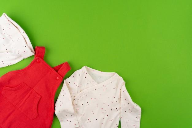 Вид сверху детской одежды на зеленом