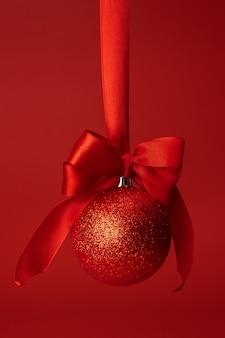 Красивая рождественская безделушка висит на красной атласной ленте на красном