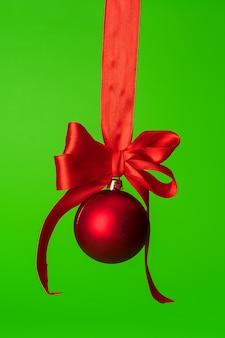 Рождественская безделушка висит на красной атласной ленте на зеленом