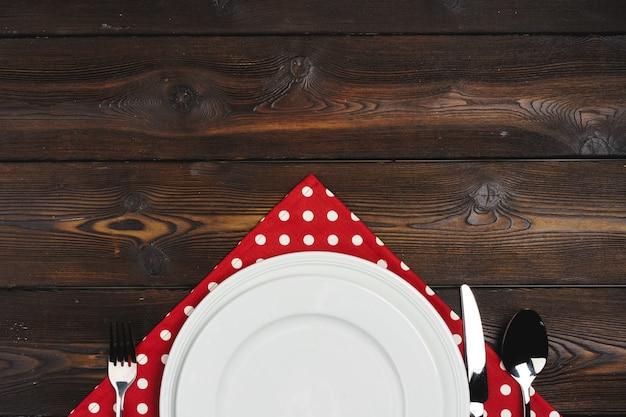 Сервировка стола с тарелками на темных деревянных
