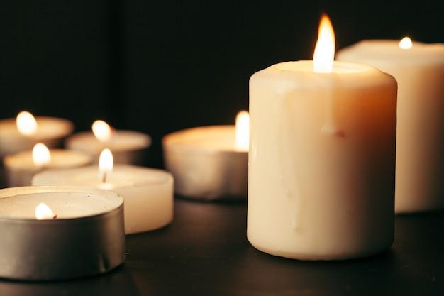 夜に燃える多くのキャンドル。暗闇で輝く多くのろうそくの炎