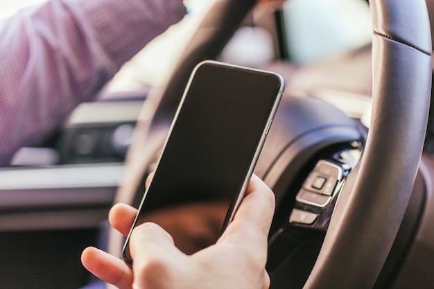 Закройте руки молодого человека с смартфон вождения автомобиля
