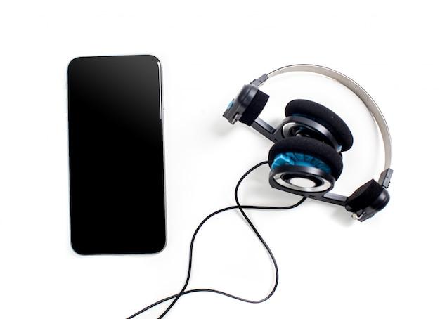 白い表面に分離されたヘッドフォンのオーディオプレーヤー