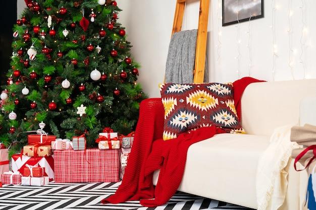 モミの木と白いソファのある美しく装飾されたクリスマスルーム