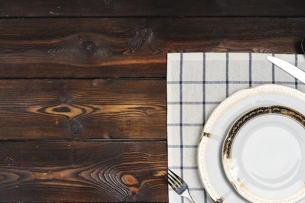 Сервировка стола с тарелками на темном деревянном столе
