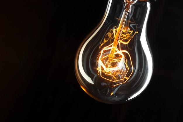 テキスト用のスペースと暗闇の古典的なエジソン電球