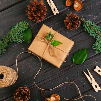 クリスマスの組成物。クリスマスプレゼント、ニットブランケット、松ぼっくり、木製のモミの枝。