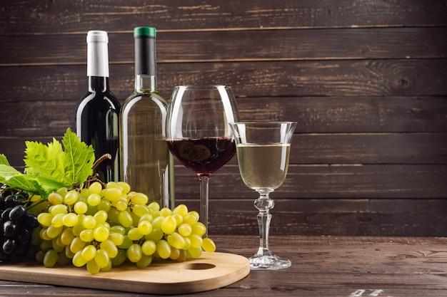 ワインの瓶と木製のテーブルのブドウ