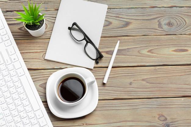メガネと文房具の木製デスクトップの平面図をクローズアップ。モックアップ