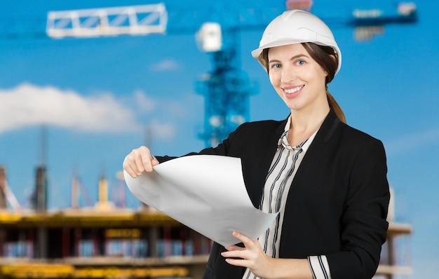 Портрет молодого женского инженера нося шлем безопасности на месте работы