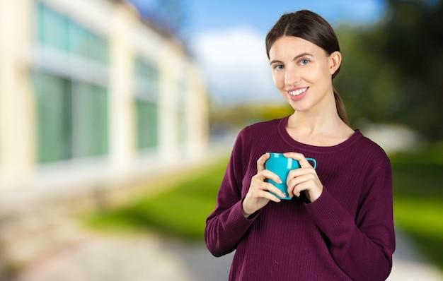 Кофе молодого и красивого портрета женщины выпивая