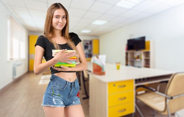 Портрет счастливой девушки или женщины студента с книгами в библиотеке