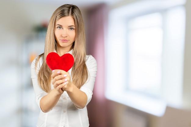 Девушка с счастливым романтичным лицом держит мягкое игрушечное сердце руками