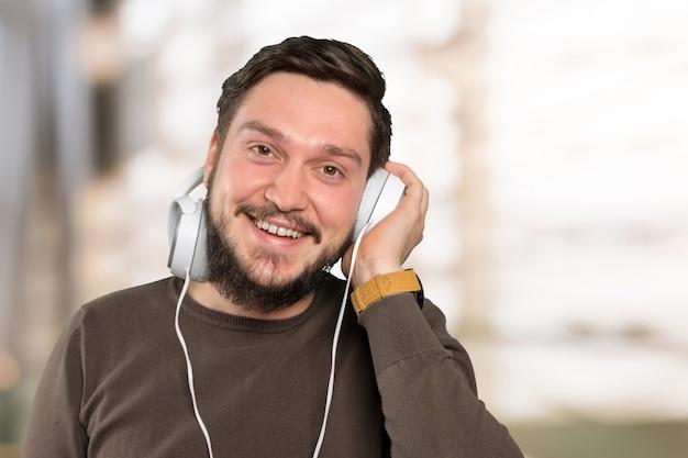 彼のスマートフォンで音楽を聞いている男性