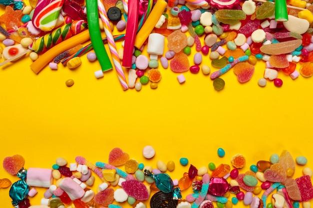 Разноцветные конфеты на желтом