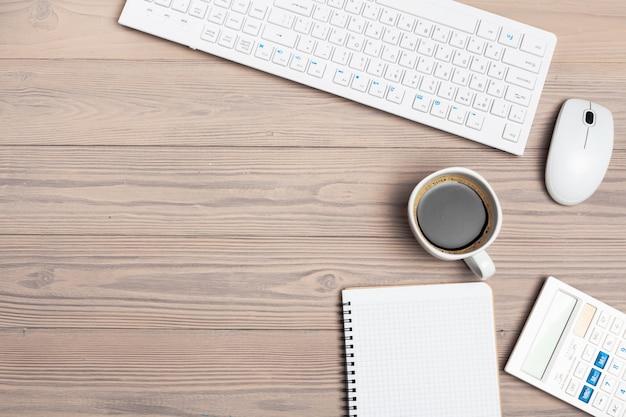 Офисное оборудование, такое как клавиатура компьютера и другие принадлежности на деревянный стол