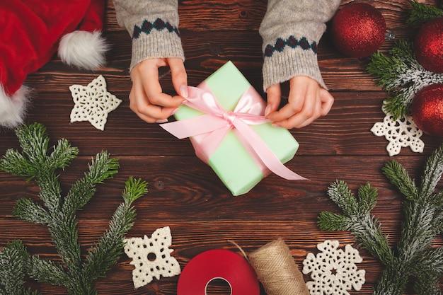 クリスマスの装飾と木製のテーブルに贈り物を持ってセーターの手