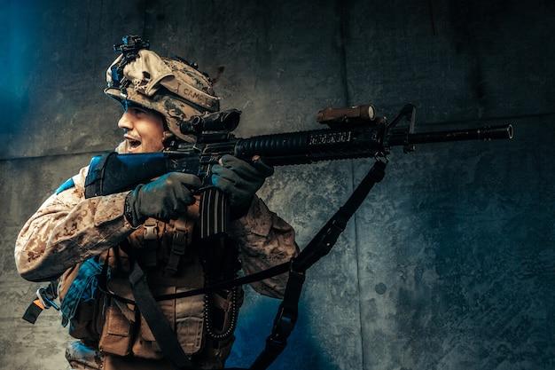 Молодой человек в военной форме наемного солдата в современное время на темноте в студии
