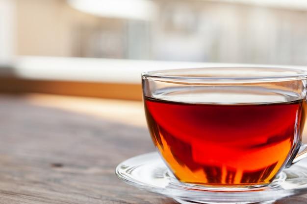 Горячая чашка чая на деревянном деревенском столе крупным планом