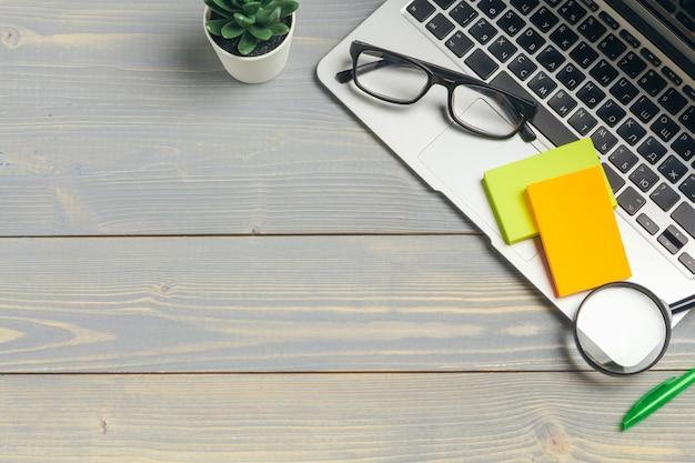 ラップトップコンピューターのキーボードと木製の机の上のさまざまな事務用品とメガネの斜めビュー