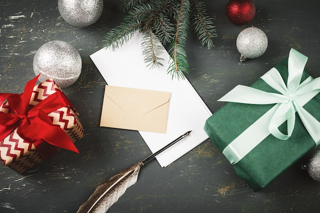 季節の装飾に囲まれた手紙、封筒、羽ペンでクリスマス