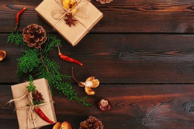 クリスマス組成、クリスマスギフト、ニットブランケット、松ぼっくり、木製の背景にモミの枝、