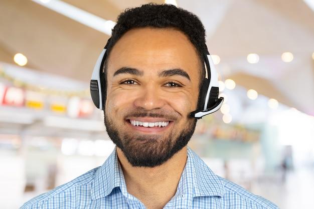彼の頭にヘッドフォンを持つ企業のプロフェッショナルコールセンターエージェント